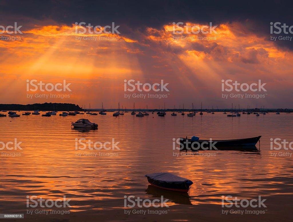 Sun rays illuminate boats in Poole Harbour stock photo