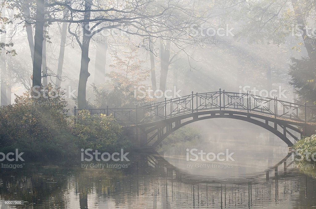 Sun rays on an old bridge over water in a park in autumn stock photo