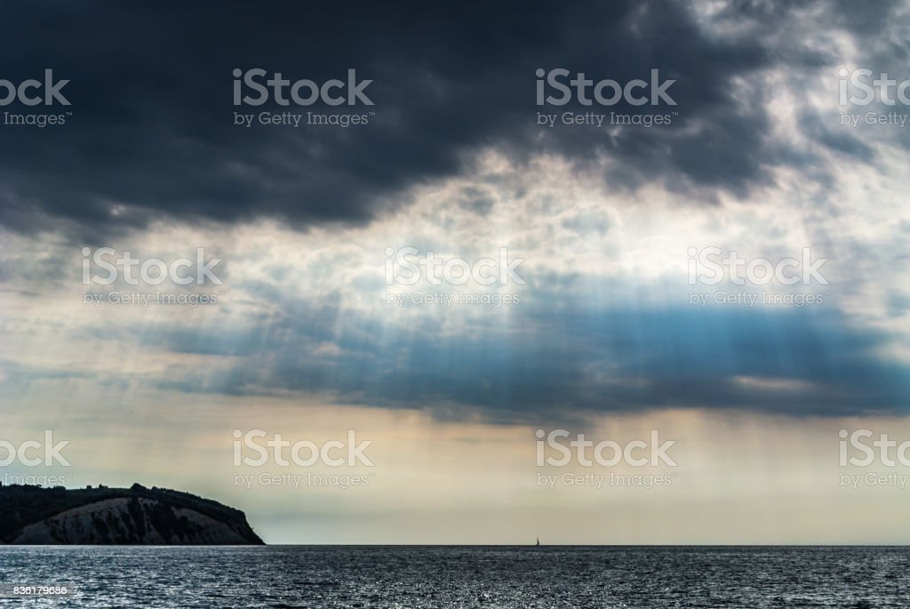 Sun rays on dark cloudy sky stock photo
