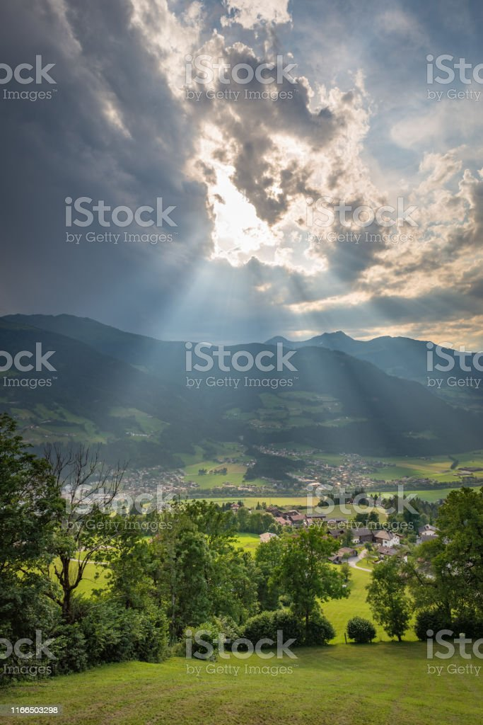 Optical phenomena called crepuscular rays over the mountains in...