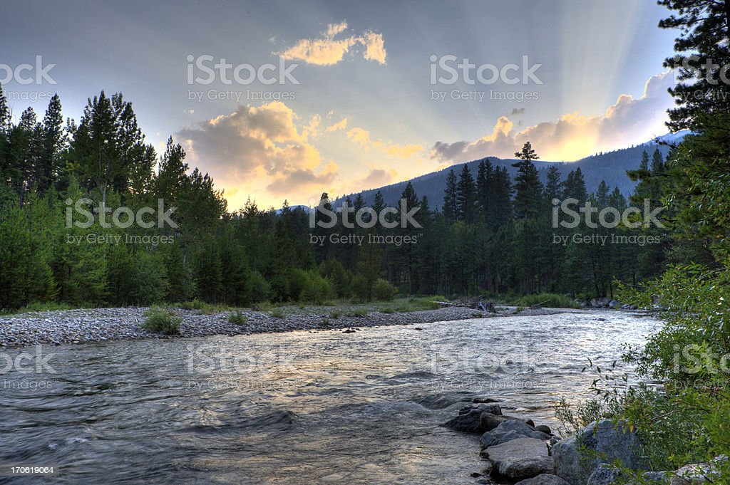 Sun rays over the River The rays of the setting sun illuminate the sky over the bitteroot river. Backgrounds Stock Photo