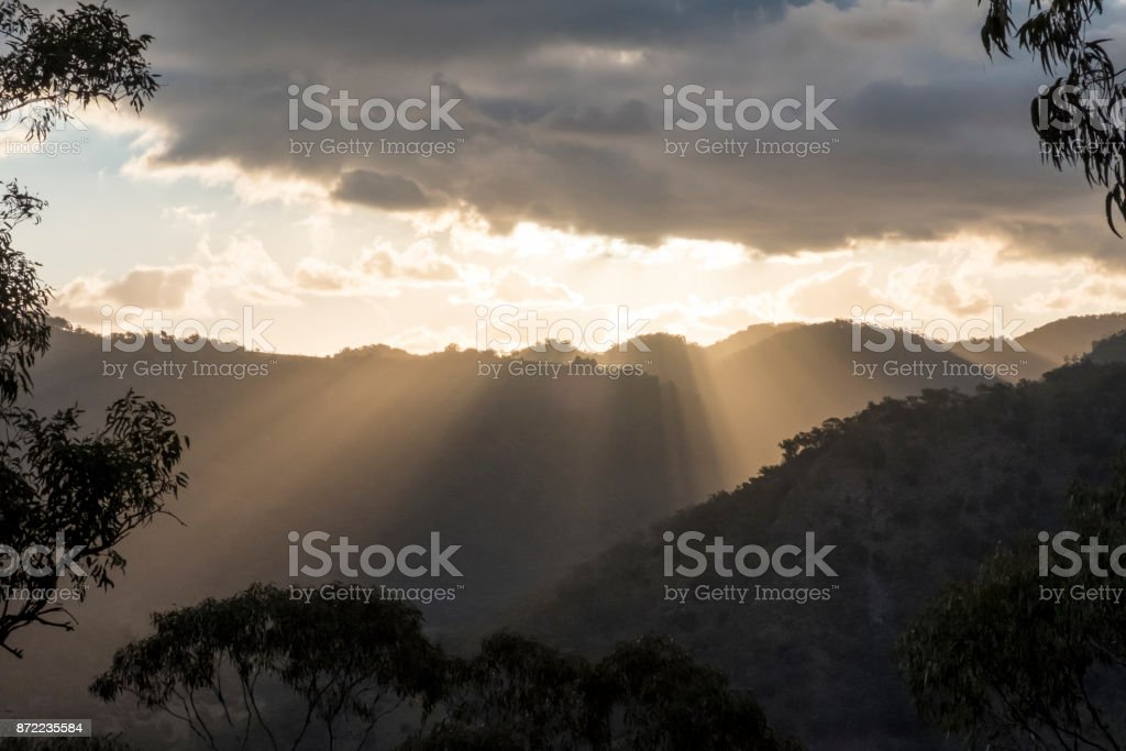 Sun rays peaking over a Southern Highland's mountain range at sunset stock photo