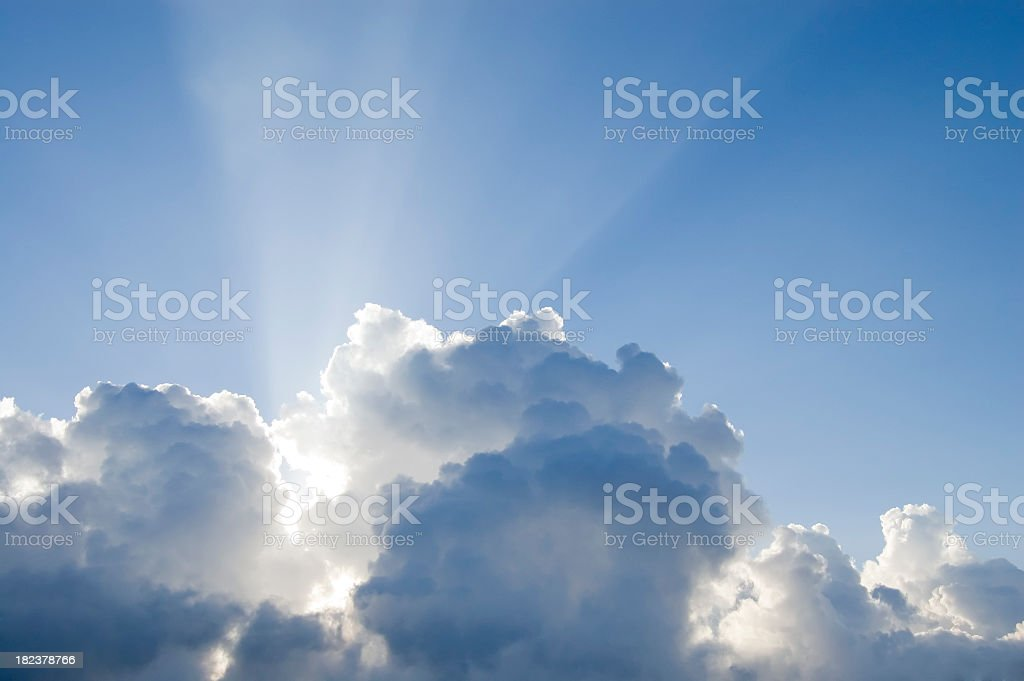 Sun rays permeating from thick white clouds stock photo