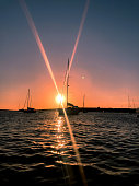 Sunset on the high seas surrounded by sailboats