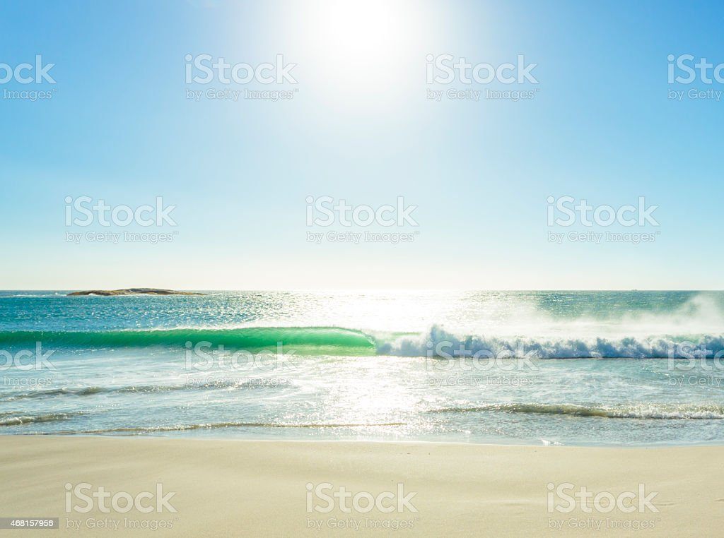 Sun reflecting in sea waves on a sunny beach. stock photo