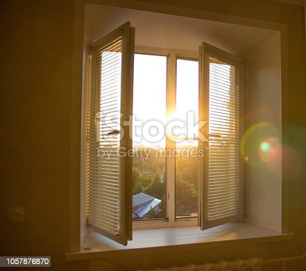istock sun rise behind the window blinds and curtains shades 1057876870
