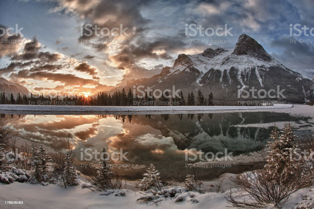 Sun rises above mountain lake, after snowfall stock photo