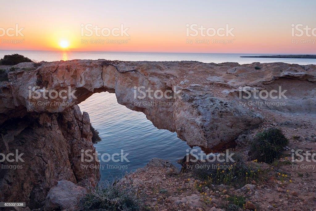 Sun rises over the stone natural bridge stock photo