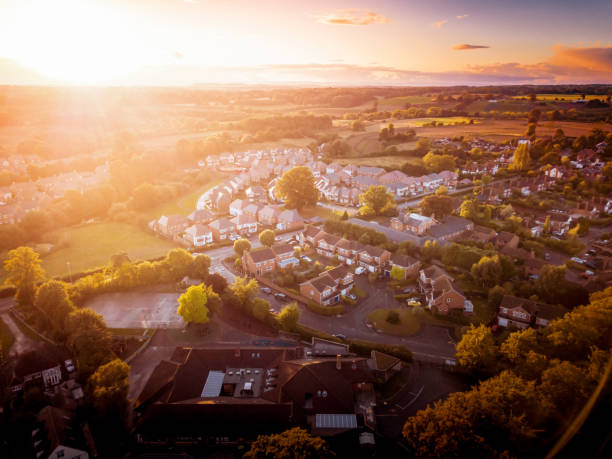 Sun rising above a traditional British housing estate with countryside in the background. Dramatic, warm lighting creates a homely mood. Very typically English houses that are over 100 years old. A picturesque scene, created by the long shadows and warm glow. residential district stock pictures, royalty-free photos & images