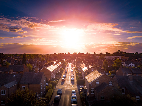 Sun rising above a traditional British housing estate with countryside in the background.