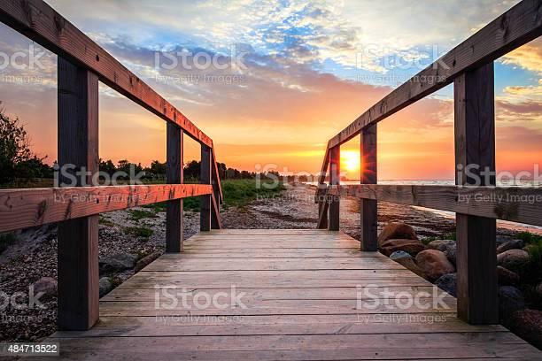 Photo of Sun rising at beach on bridge