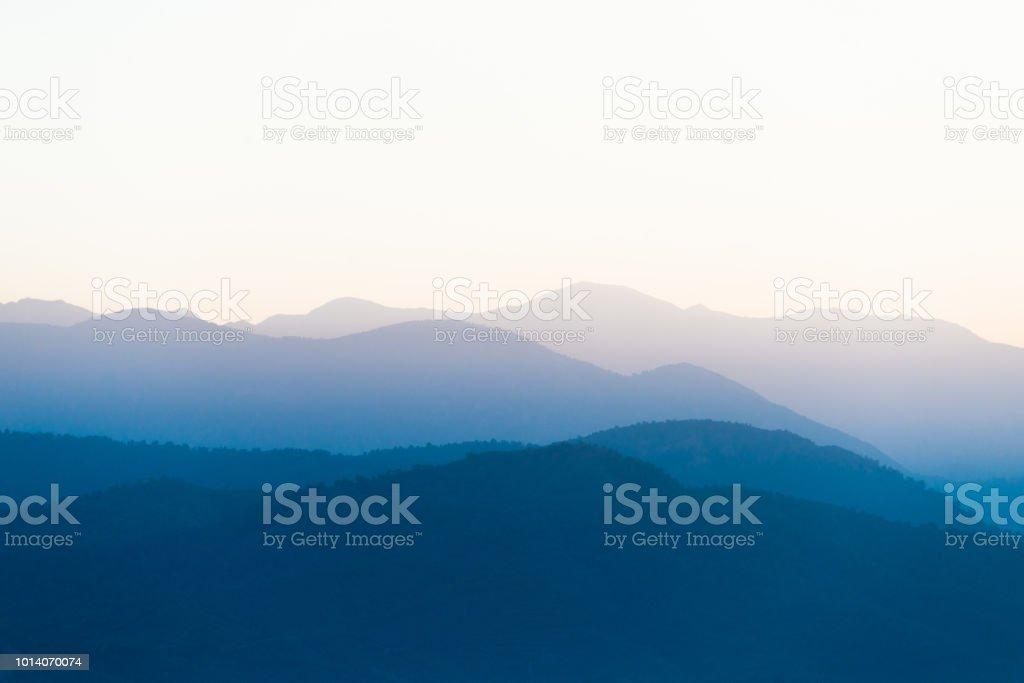 Sun rising behind a mountain ridge. stock photo