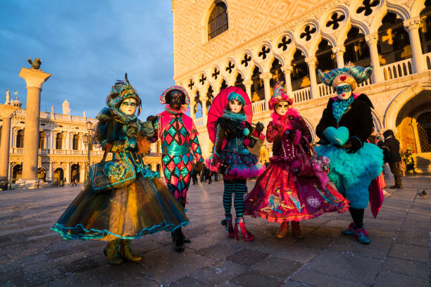 Sun rising in Venice with masks on Saint Marco Square, Italy Venice, Italy - February 06, 2018: Sun rising in Venice with Masks walking on Saint Marco Square. They are going to pier in front of anchored gondolas for action with photographers. sun shining through dresses stock pictures, royalty-free photos & images