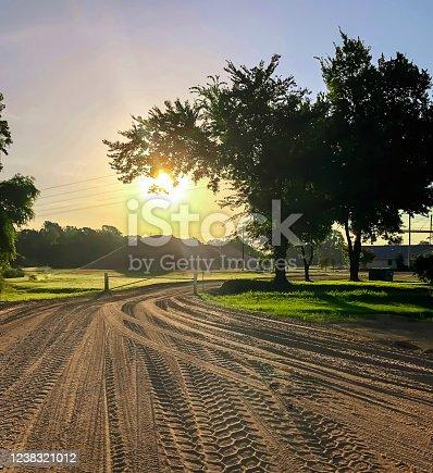 A rising sun over rural Arkansas as seen from a dirt road