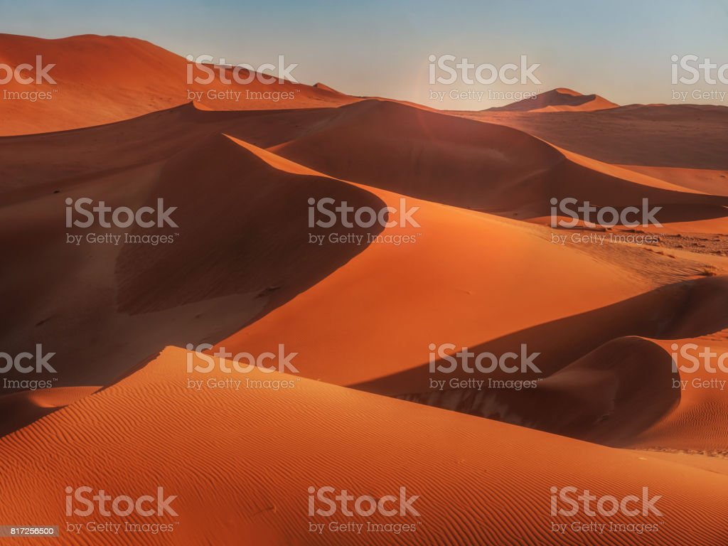 Sun rising over red sand dunes of Namibian desert. stock photo