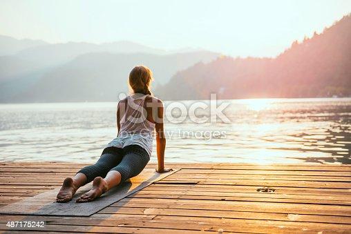 Beautiful woman practicing Yoga by the lake - Sun salutation series - Upward facing dog - Toned image