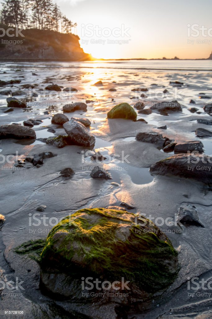 Sun set glows over rocks at low tide stock photo