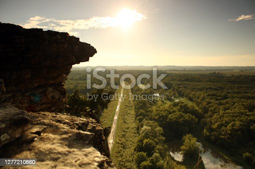 the sun setting on a cliff top with road