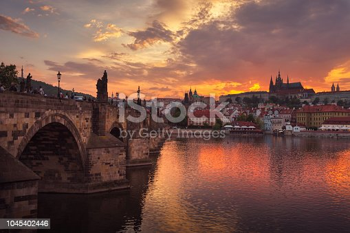 The sun sets by the historic Charles Bridge (Karluv most) leading over the Vltava river in Prague, Czech Republic. The bridge was constructed in the 14th and early 15th century. In the background is Prague Castle and St Vitus Cathedral.