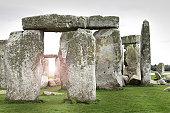 A distant view of the World Heritage site Stonehenge in Wiltshire, England looking across fields on a summer's sunrise.