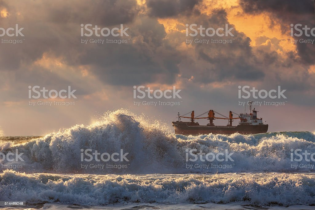Sun setting at the sea with sailing cargo ship stock photo