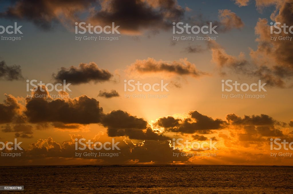 Sun setting behind dark Clouds over South Pacific Ocean stock photo