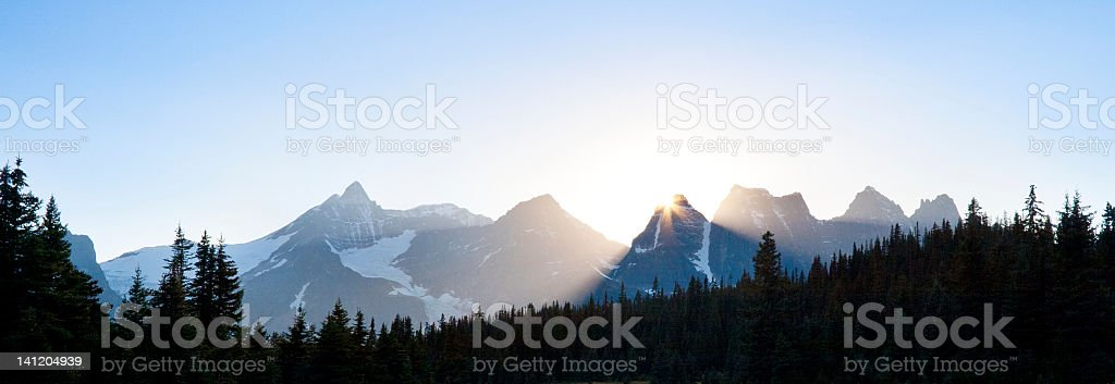 sun setting behind mountain peaks stock photo
