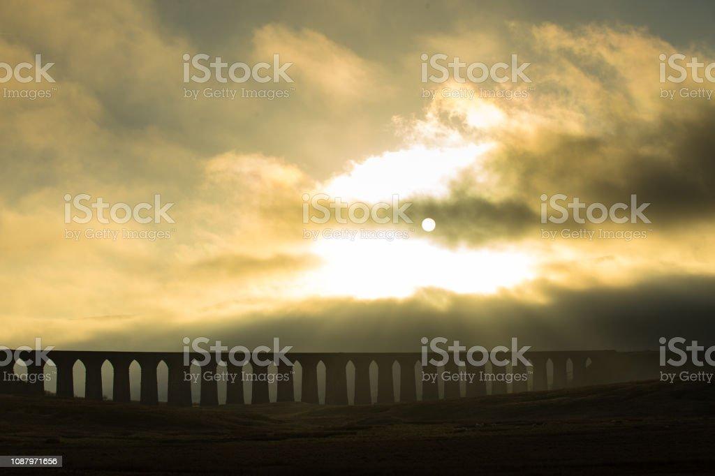 Sun Setting Behind Ribblehead Viaduct on Foggy Evening stock photo