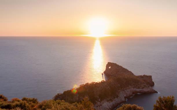 "Sun setting by the horizon line of the sea in ""Sa Foradada"", a peninsula of the Sierra de Tramuntana in Mallorca stock photo"