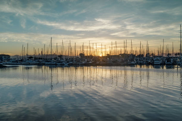 Sun setting on Emeryville Marina Sailboats moored in San Francisco Bay with sunset skies and water reflections. Alameda County, California, USA. san francisco bay stock pictures, royalty-free photos & images