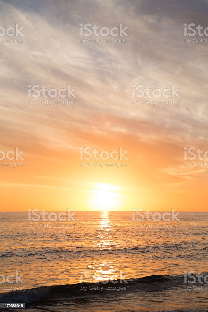 Sun Setting on Horizon over Ocean with Waves at Beach stock photo