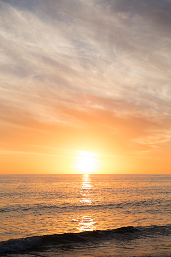 Sun Setting On Horizon Over Ocean With Waves At Beach Stock Photo - Download Image Now