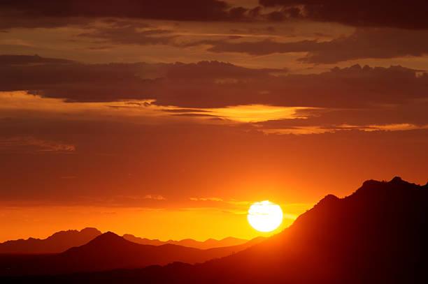 Sun setting over hills stock photo