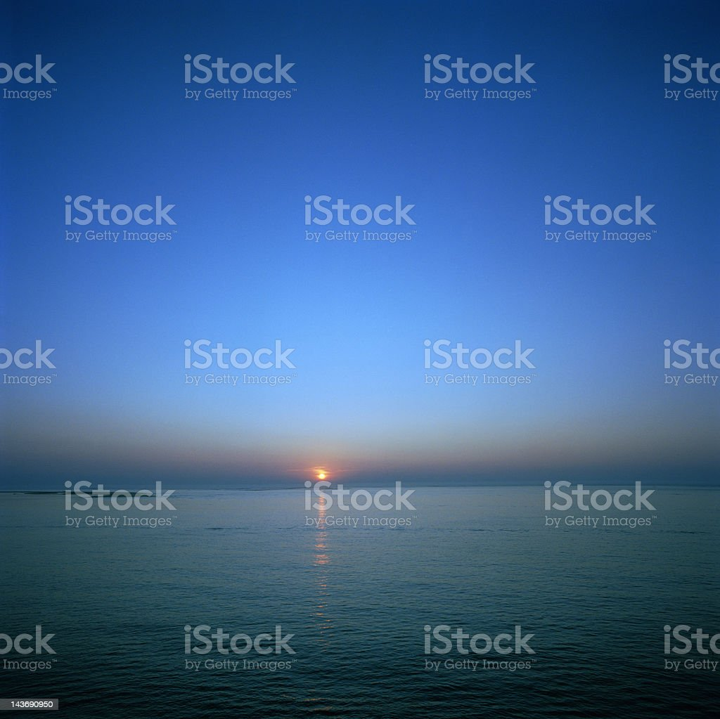 Sun setting over still waters stock photo