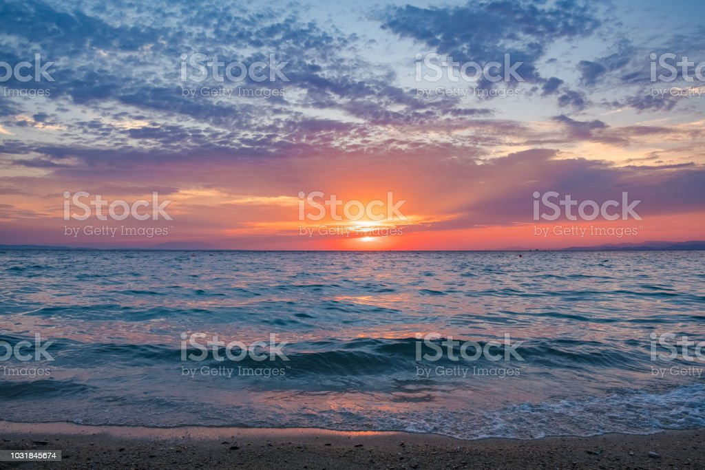 Sun setting over the horizon reflecting the sea stock photo