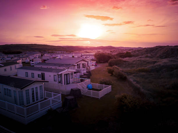 Sun Setting over the sea and Caravan and camping park, static home aerial view. Porthmadog holiday park taken from the air by a drone showing holiday houses and British holiday lifestyle. trailer park stock pictures, royalty-free photos & images