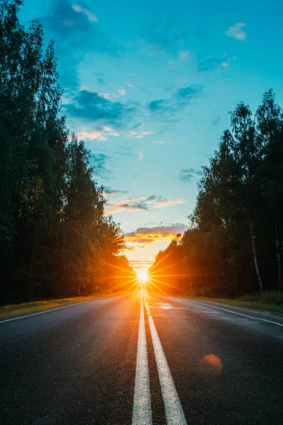 Sun Shine Above Asphalt Country Open Road In Sunny Morning Or Evening. Open Free Road In Summer Or Autumn Season At Sunny Sunset Or Sunrise Time stock photo