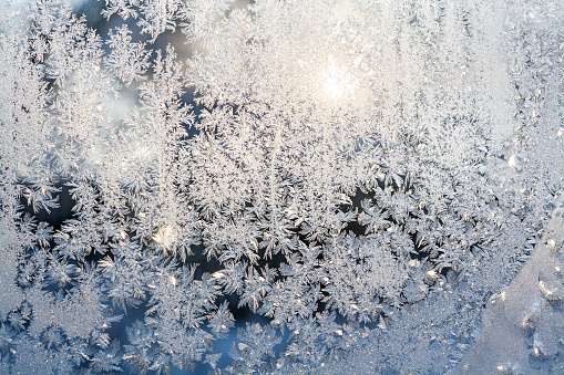wintry frosty pattern on glass. abstract background of ice frozen window. winter day, sun shine through frosted glass on window.