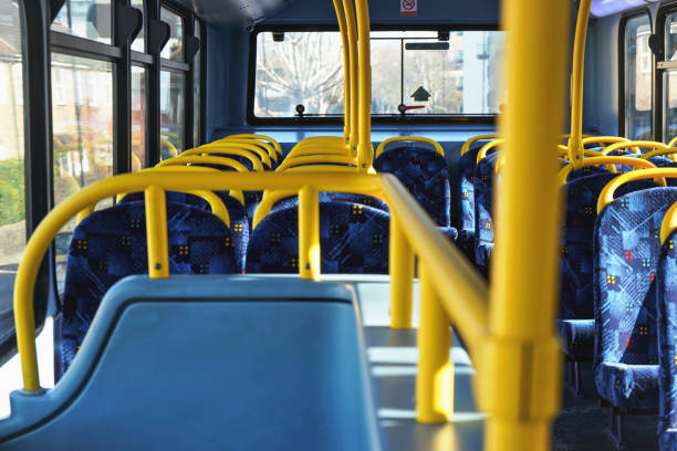 Sun shines on empty interior of London double decker bus, yellow holding rails and blue seats stock photo