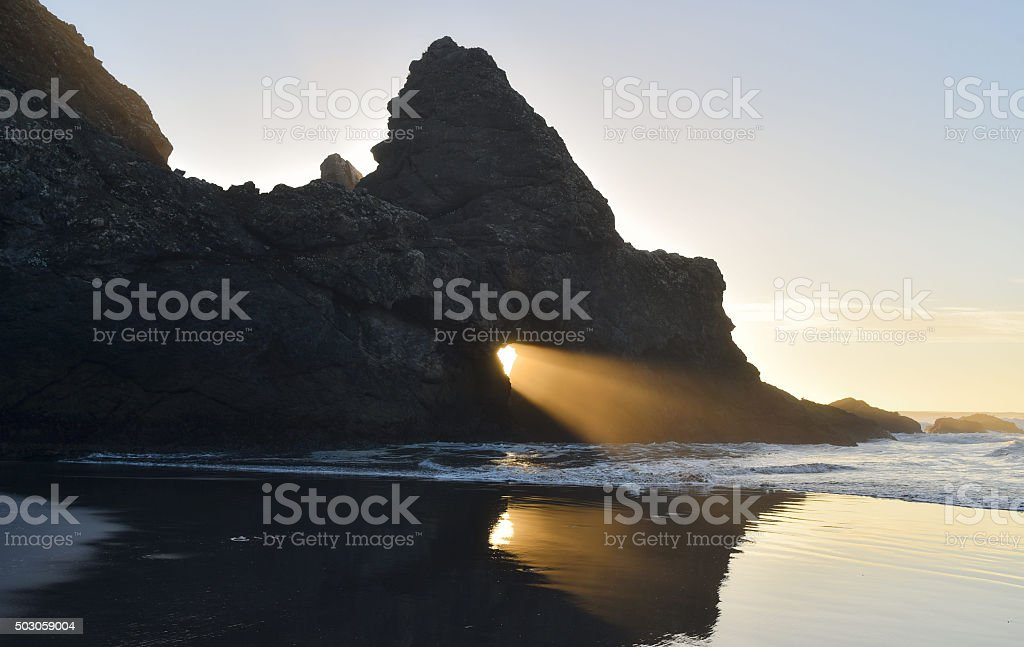 sun shines through hole in rock on beach stock photo