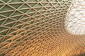 Sun shines through the triangulated roof at Kings Cross Station in London, United Kingdom