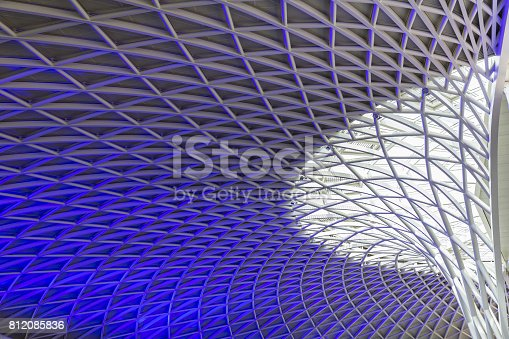Sun shines through the triangulated roof at Kings Cross Station in London