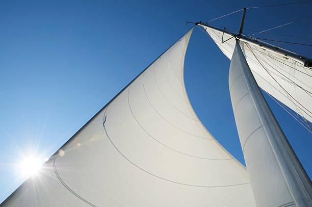 sonne scheint hinter der segeln auf einer yacht - segeln stock-fotos und bilder