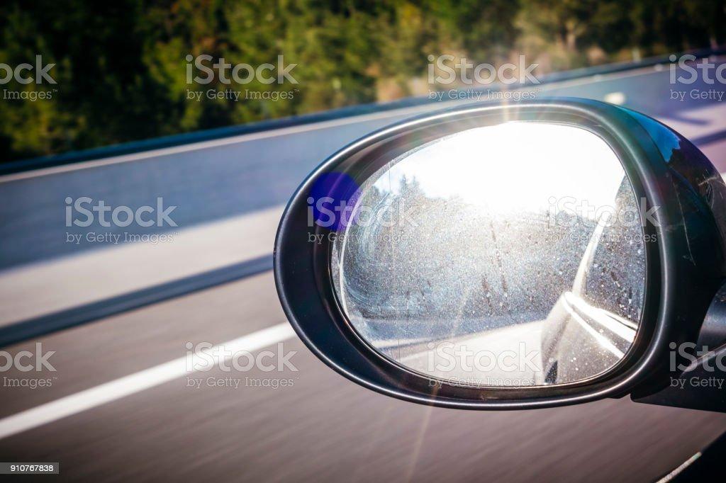 Sun shining on a left black mirror car on a highway stock photo