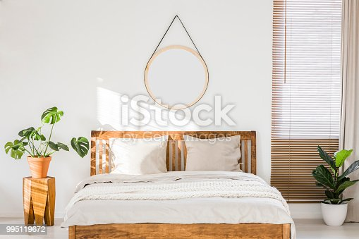 istock Sun shining on a white wall with a round mirror in a minimalist bedroom interior with natural, wooden furniture and beautiful green plants 995119672