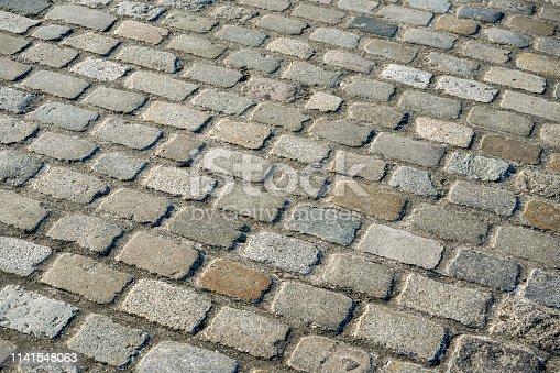 Sun shining on tile stone road texture
