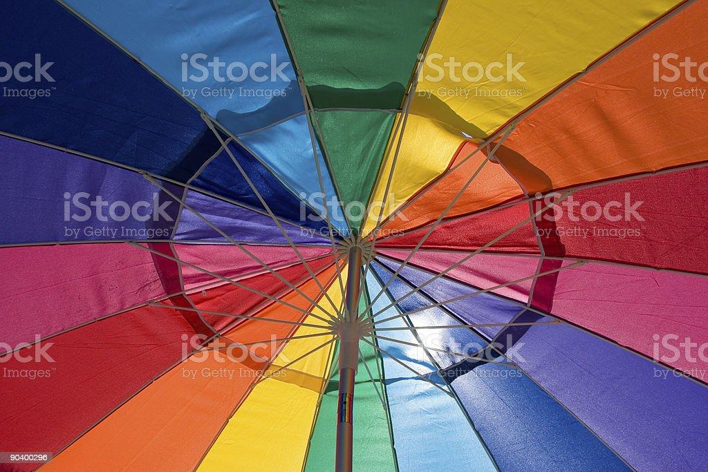 Sun shining through a bright rainbow colored cafe umbrella royalty-free stock photo