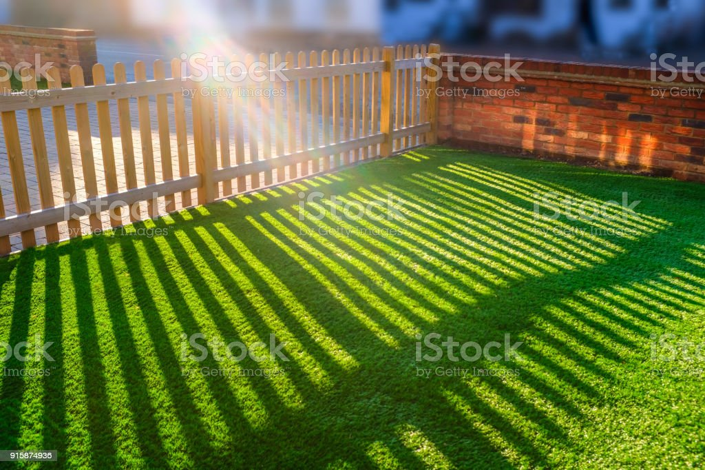 sun shining through a wooden picket fence onto an artifical grass lawn stock photo