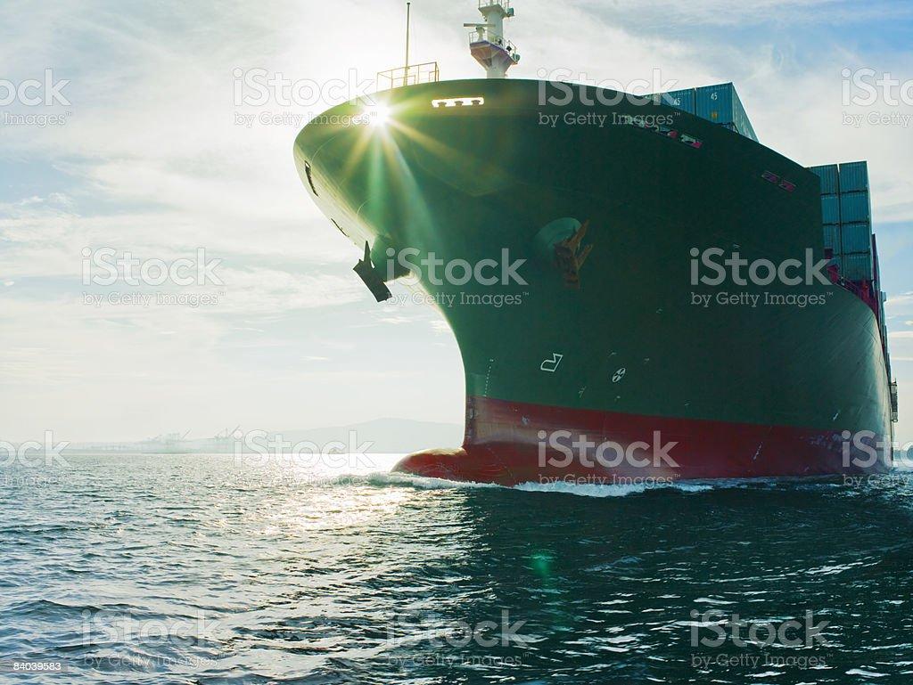 Sun shining through bow of cargo ship stock photo