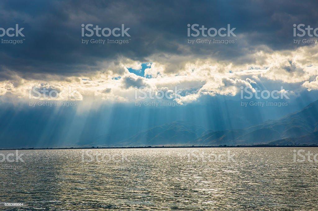 Sun Shining Through Clouds Over Lake